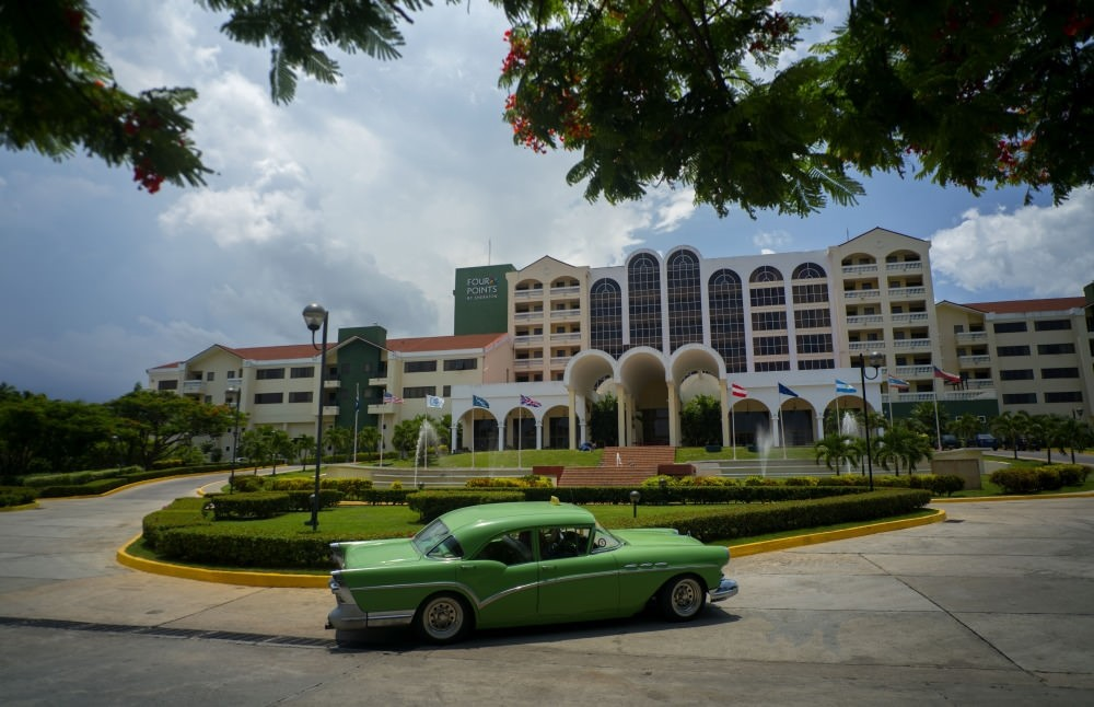 A vintage car passes in front of the Four Points by Sheraton hotel in Havana, Cuba. American hotel giant Starwood has begun managing this hotel owned by the Cuban military.