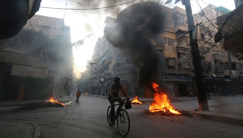 A man rides a bicycle past burning tyres, which activists said are used to create smoke cover from warplanes, in Aleppo, Syria August 1, 2016 (Reuters Photo)