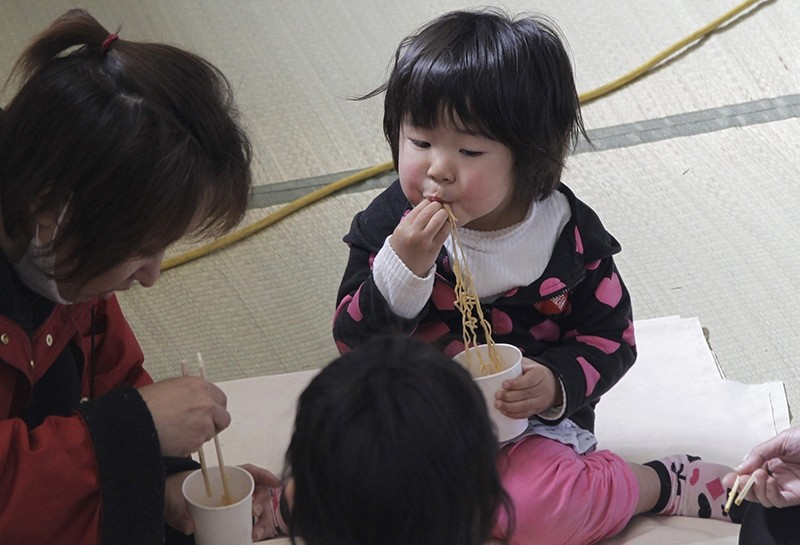 A child eats noodle during a lunch at an evacuation center in Ofunato, Iwate Prefecture, Japan, Sunday, March 20, 2011 (AP Photo)