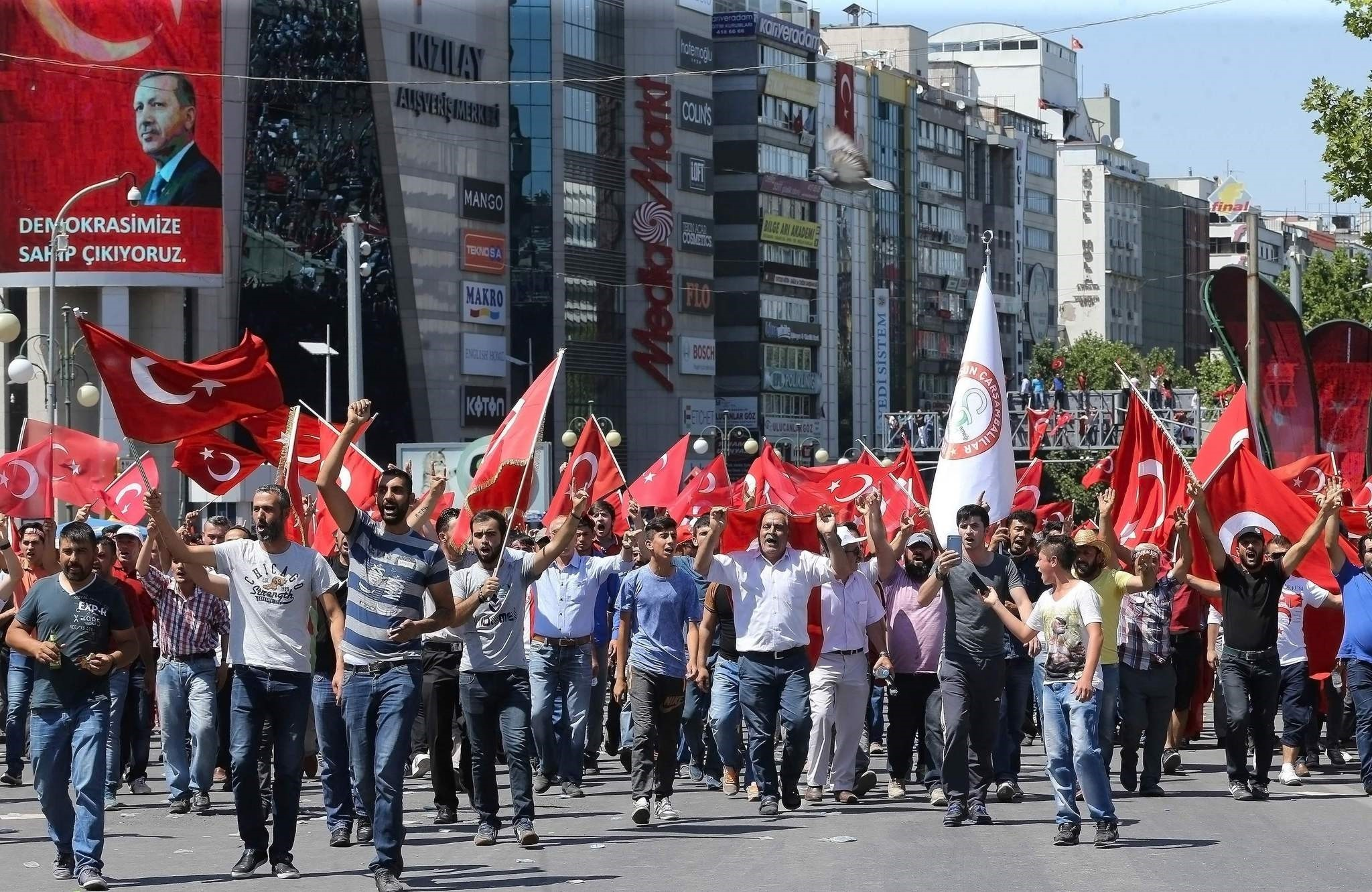 People wave national flags as they march from Kizilay square to Turkish General Staff building to react against military coup attempt, in Ankara, on July 16, 2016.