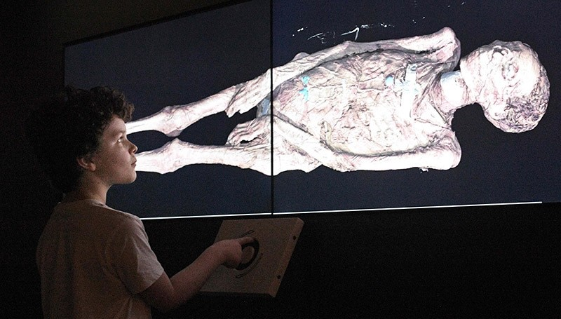 A young boy looks at a three-dimensional image of a CT scan of an Egyptian mummy at a joint British-Australian exhibition in Sydney on December 8, 2016. (AFP Photo)