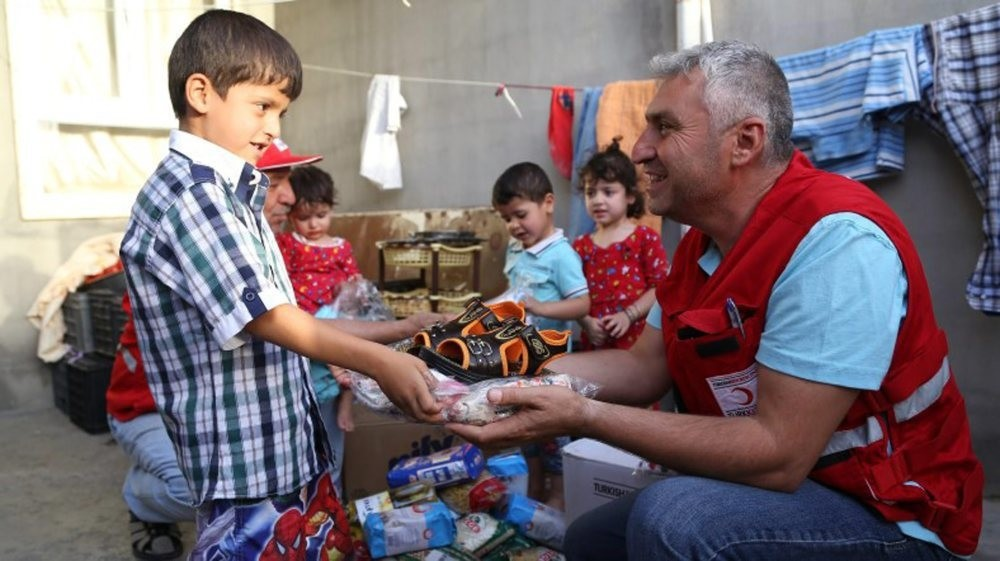 A Turkish Red Crescent worker delivers aid to Iraqi children. The Red Crescent was among the sponsors of the forum, where redefining priorities for humanitarian aid was discussed.