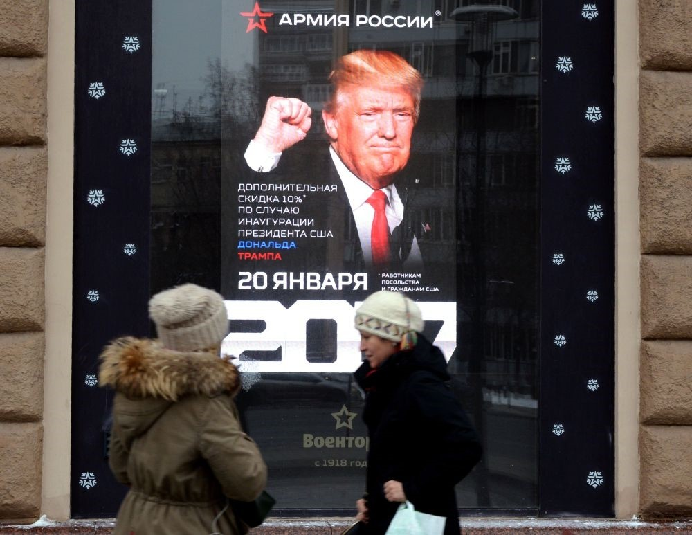 Women walk past a screen displaying a portrait of U.S. President-elect Donald Trump installed inside a Voentorg shop window in central Moscow