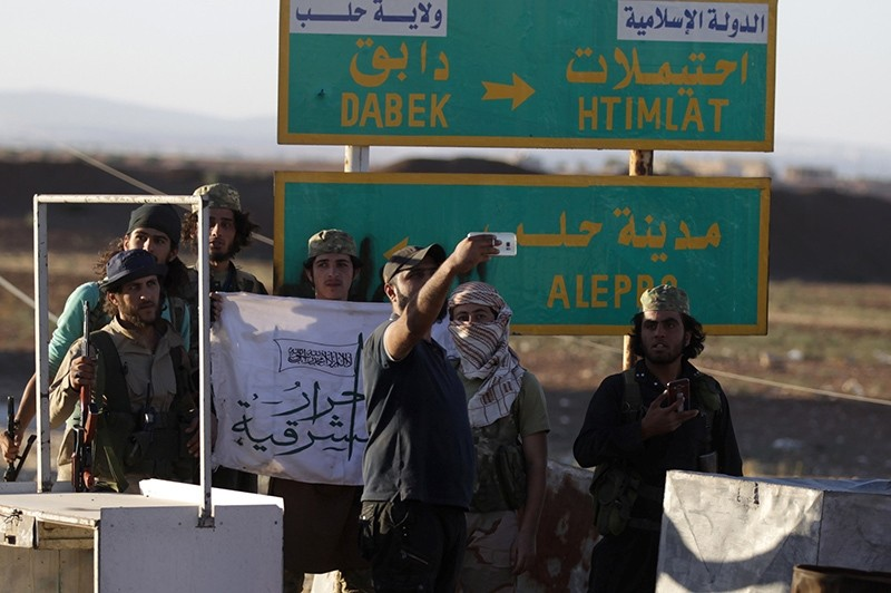 Rebel fighters take a selfie near a road sign in Dabiq town, northern Aleppo countryside, Syria October 16, 2016 (Reuters Photo)