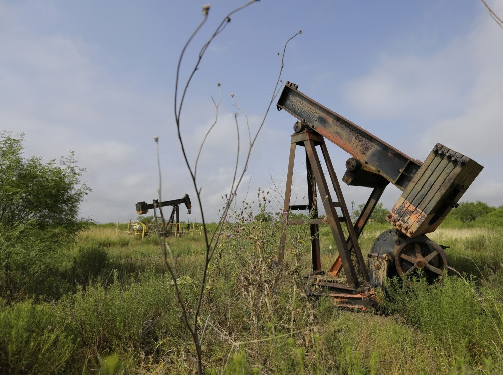 Pumps sit idle on a South Texas ranch. Deserted drilling wells are the relics of every oil bust, and Texas is pitted with more than any other place in the U.S.