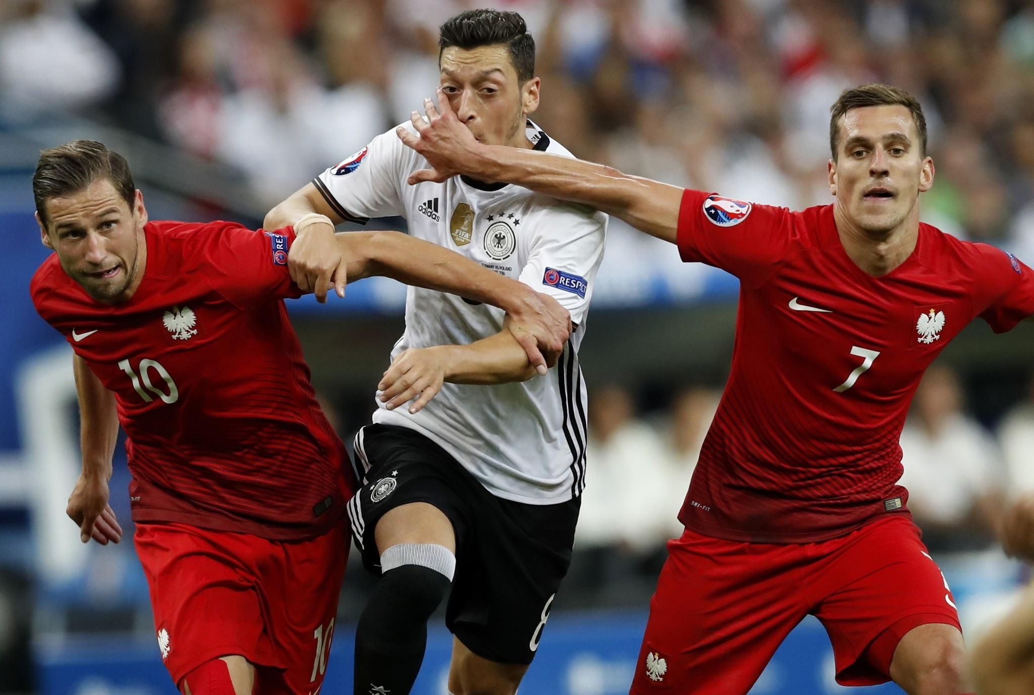 Germany's Mesut Ozil, center, is challenged by Poland's Grzegorz Krychowiak, left, and Poland's Arkadiusz Milik during the Euro 2016 Group C soccer match. (AP Photo)
