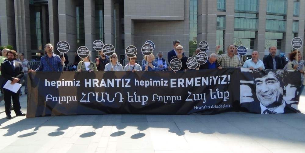 Activists hold a banner with a photo of Hrant Dink and a slogan: ,We are all Hrant,, outside the courthouse in Istanbul.