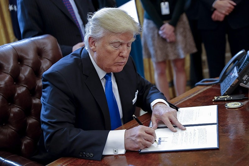 US President Donald Trump signs one of five executive orders related to the oil pipeline industry in the oval office of the White House in Washington, DC, USA, 24 January 2017. (EPA Photo)