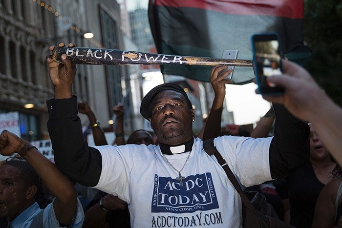 A man holds a bat reading ,Black Power, during a protest in Dallas, Texas, on Thursday, July 7, 2016 to protest the deaths of Alton Sterling and Philando Castile. (AFP Photo)