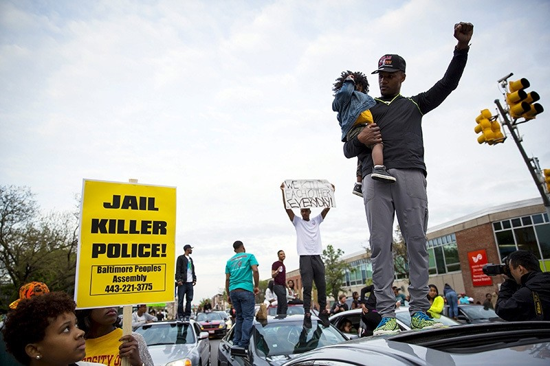 Demonstrators stand on top of vehicles at the intersection of North Avenue and Pennsylvania Avenue in Baltimore, Maryland May 1, 2015. (Reuters Photo)