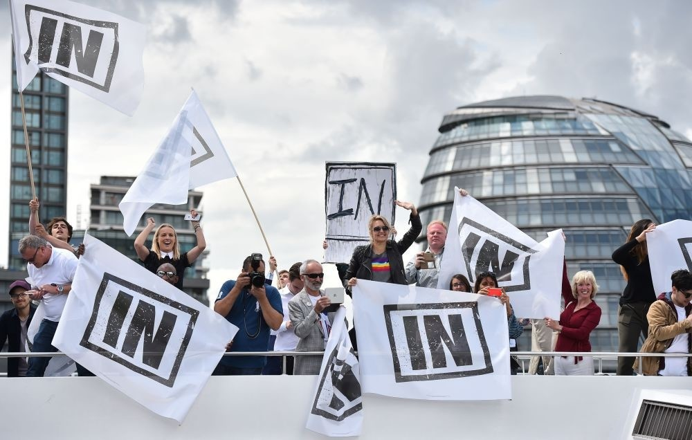 A boat carrying Remain supporters shout and wave at Brexit fishing boats as they sail up the River Thames in central London on Wednesday.