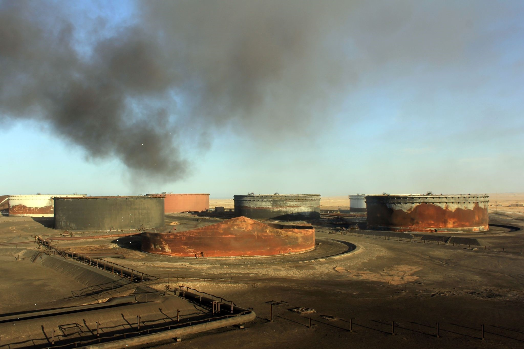 This file photo taken on January 8, 2016 shows smoke billowing from a petroleum storage tank after a fire was extinguished following fighting at Al-Sidra oil terminal. (AFP Photo)