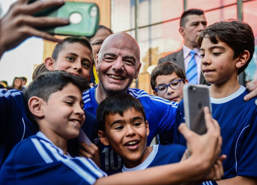 FIFA's President Gianni Infantino takes selfies during a friendly football match with former Colombian players and international football stars in Bogota.