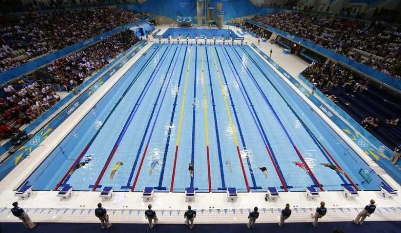 Swimmers dive into the water to start the womenu2019s 50m freestyle event during the London 2012 Olympic Games.