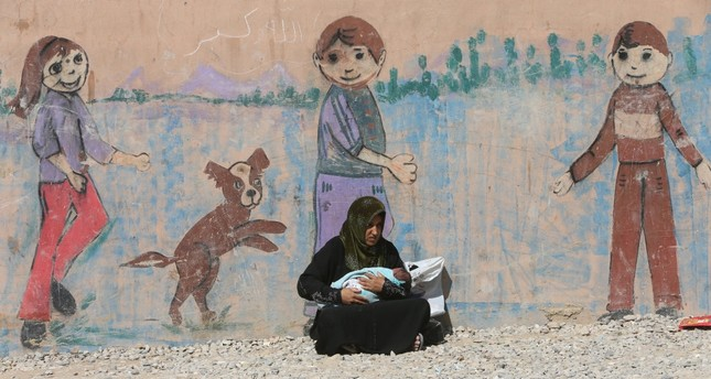 A displaced woman, who fled from Daesh terrorists in Mosul, holding her baby at Deepaka camp in the northwest of Irbil, during an operation against Daesh in Mosul, Iraq, Oct. 20, 2016.