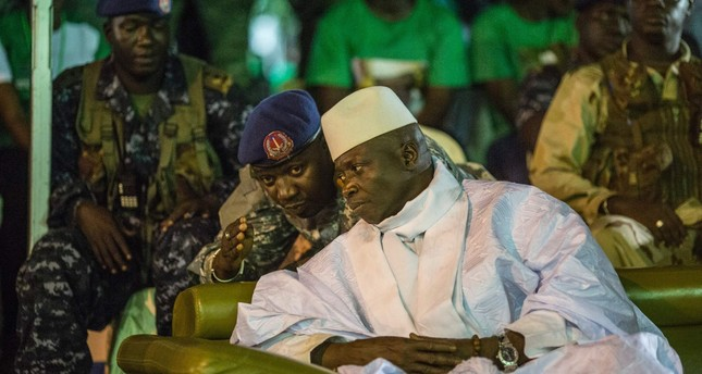 Gambian President Yahya Jammeh listening to one of his aides in Banjul, during the closing rally of the electoral campaign. (AFP Photo)