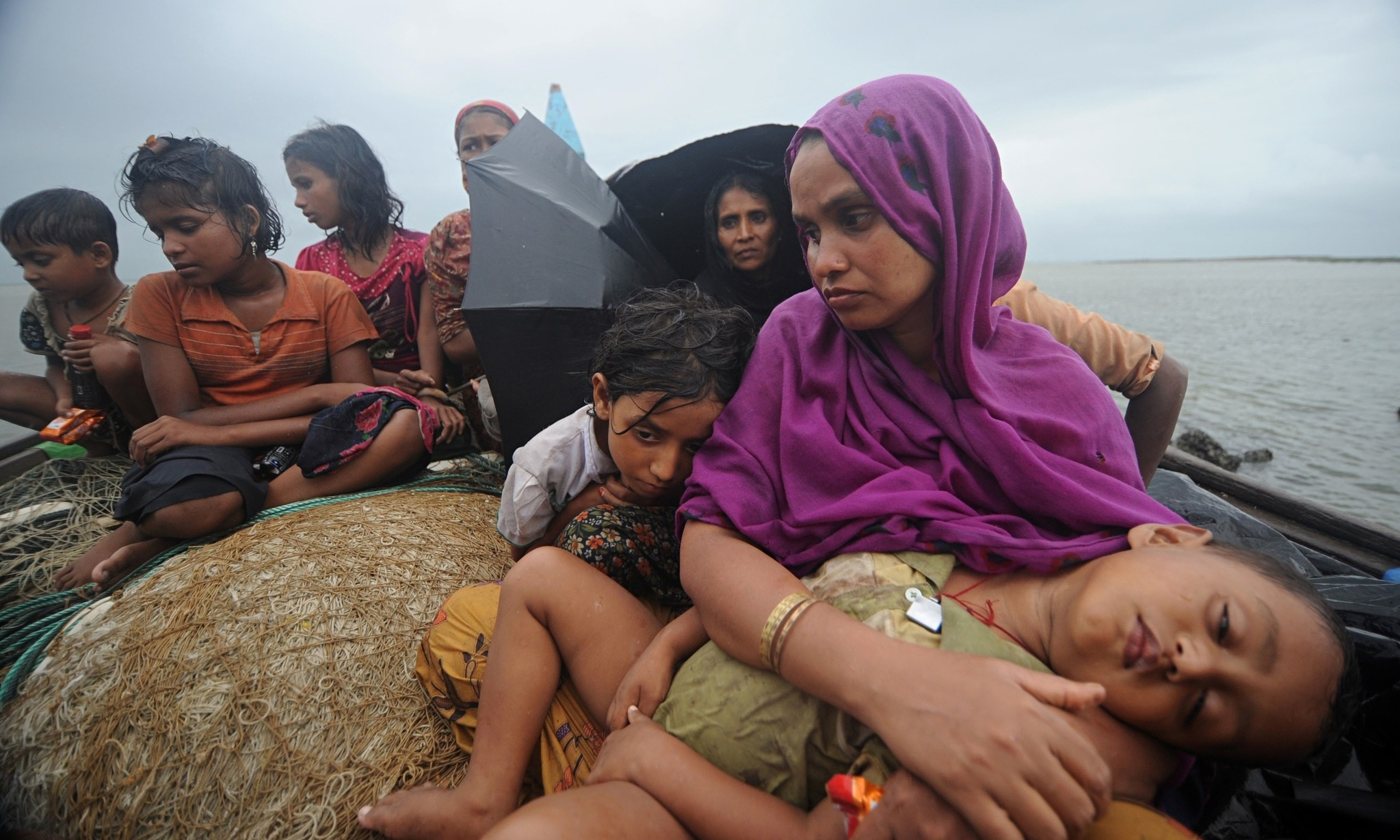 Rohingya Muslim women and children sit in a boat after they were intercepted by the Bangladesh Border Guard (BGB) members in Teknaf, Bangladesh.