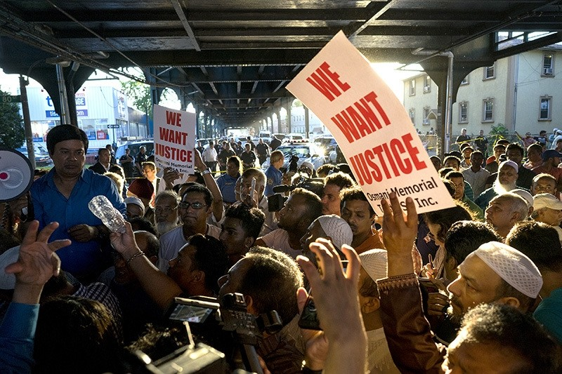 People gather for a demonstration Saturday, Aug. 13, 2016, in the Queens borough of New York, near a crime scene after the leader of a New York City mosque and an associate were fatally shot as they left afternoon prayers. (AP Photo)