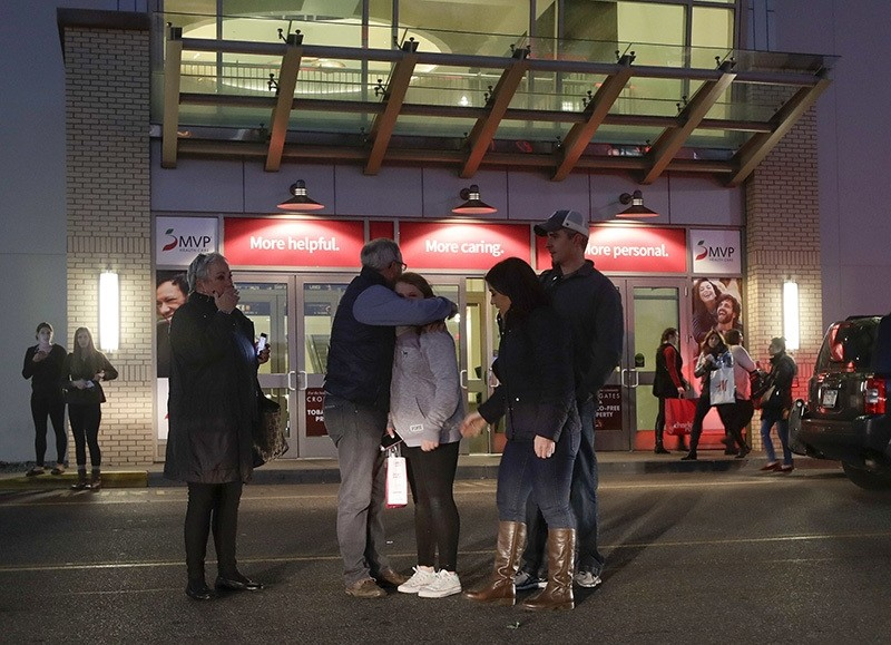 People embrace after leaving Crossgates Mall in Guilderland, N.Y., after reports of gunfire inside, Saturday, Nov. 12, 2016. (AP Photo)
