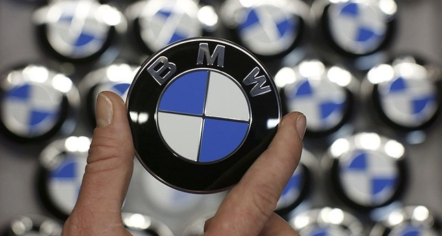 An employee holds a BMW logo on the production line of the BMW C Evolution Electric Maxi-Scooter at the BMW Berlin motorcycle plant February 23, 2015. (Reuters Photo)