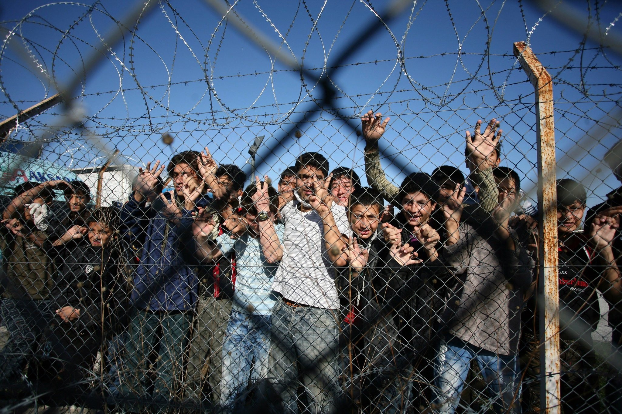 Immigrant minors peer out through the fence of an immigrant detention center in the village of Filakio, on the Greek-Turkish border. (AFP Photo)