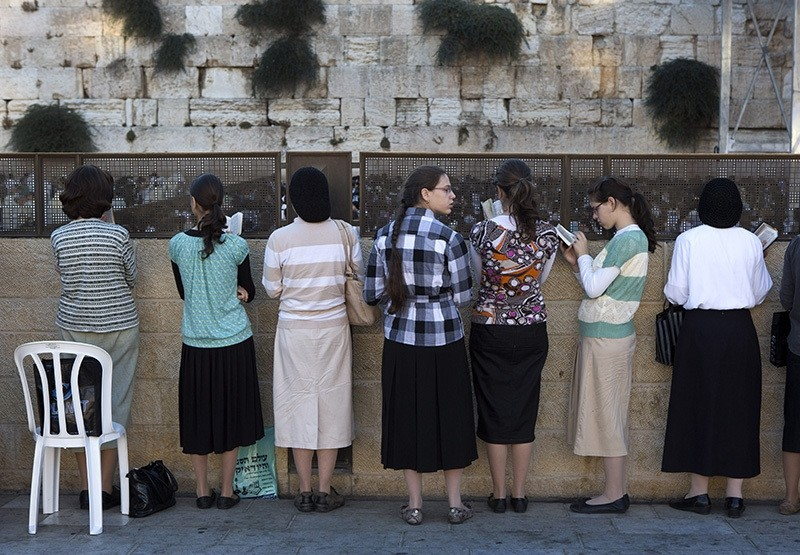 Orthodox Jewish women reading from prayer books behind a large crowd of women packing the women's section of the Western Wall in Jerusalem's Old City (EPA Photo)