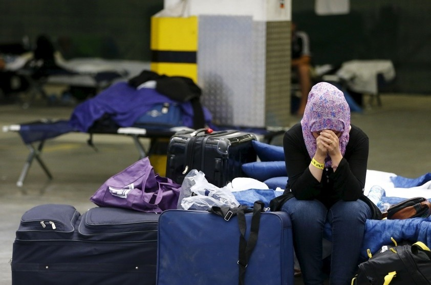 A Syrian sits on a folding bed in a former newspaper printing house being used as a refugee registration center in Frankfurt.
