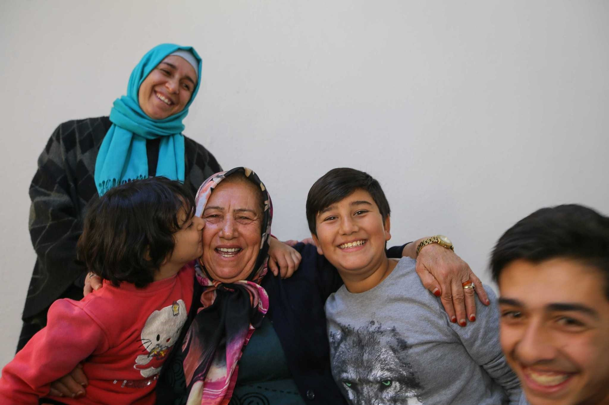 Children of the Syrian family embrace and kiss Nabiha Acar who has helped them since they settled in u0130zmir.