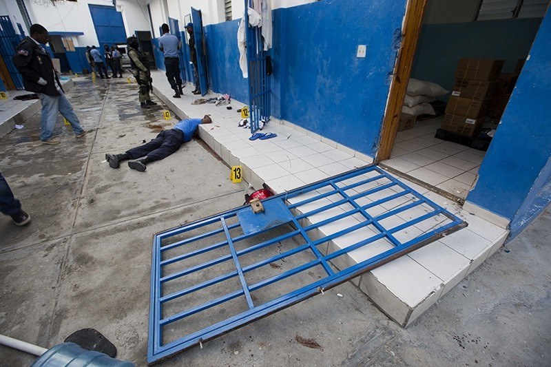 A guard lies dead inside the Civil Prison after a jail break in the coastal town of Arcahaie, Haiti, Saturday, Oct. 22, 2016. Over 100 inmates escaped after they overpowered guards who were escorting them to a bathing area. (AP Photo)
