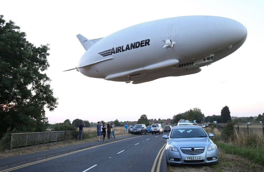 The Hybrid Air Vehicles HAV 304 Airlander 10 hybrid airship is seen in the air over a road on its maiden flight from Cardington Airfield near Bedford, north of London.