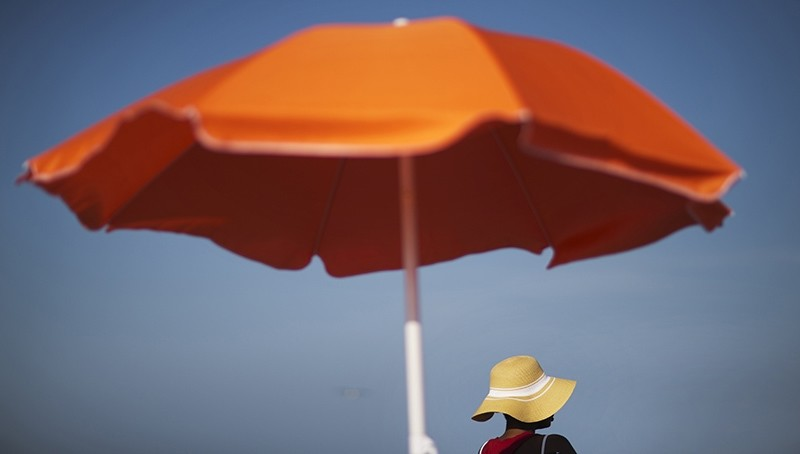 In this Tuesday, June 16, 2015, file photo, a woman sits next to an umbrella while looking out toward the ocean in Folly Beach, S.C. (AP Photo)