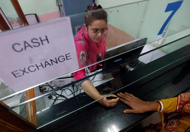 A bank employee puts indelible ink mark to a customeru2019s finger inside a bank in Kolkata, India, November 23, 2016. (Reuters Photo)