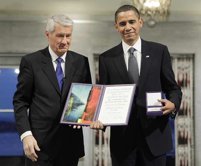 In this Dec. 10, 2009, file photo, President and Nobel Peace Prize laureate Barack Obama poses with his medal and diploma alongside Nobel committee chairman Thorbjorn Jagland at the Nobel Peace Prize ceremony at City Hall in Oslo, Norway. (AP Photo)
