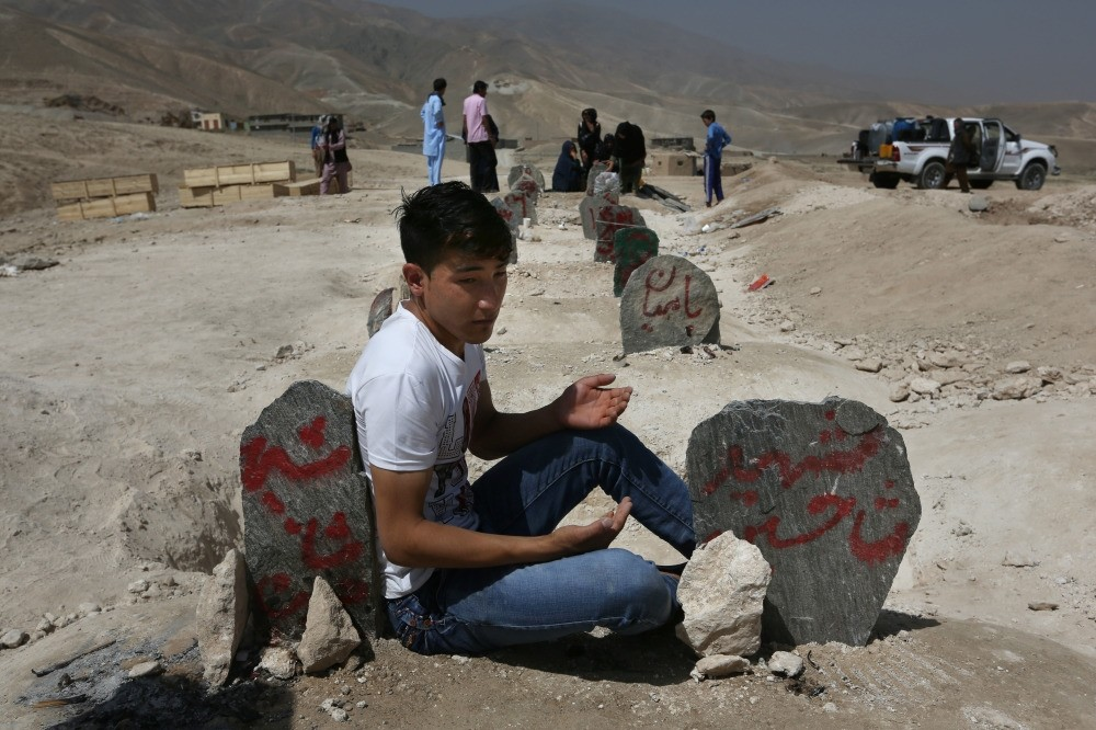A man prays in front of graves of victims of a suicide attack, Kabul, July 25.