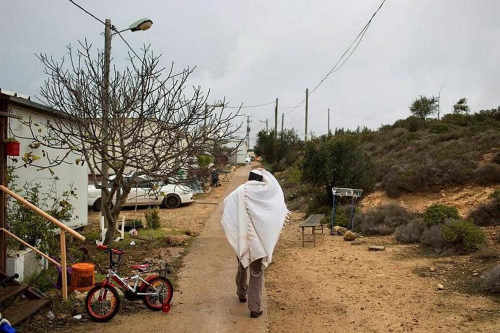 A Jewish settler covered in a prayer shawl walks back to his house in Amona, an unauthorized Israeli outpost in the West Bank.