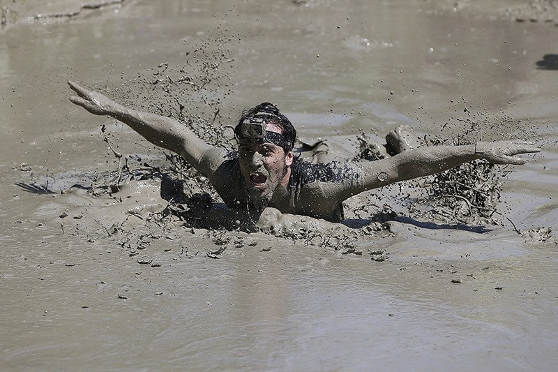 A participant swims to cross a mud pool during the Mud Day athletic event at El Goloso Military base on the outskirts of Madrid, Spain, Saturday, June 11, 2016. (AP Photo)