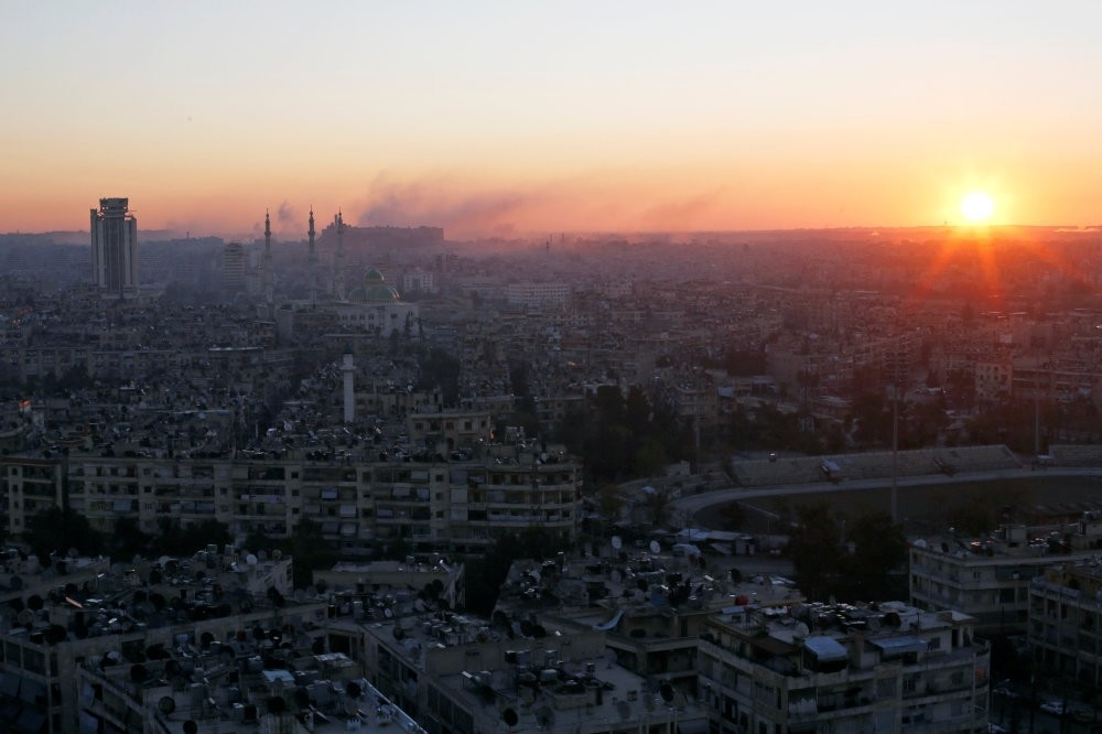 The sun rising with smoke billowing in the air near Aleppo's historic citadel, as seen from a regime-controlled area of Aleppo, Syria, Dec. 6, 2016.