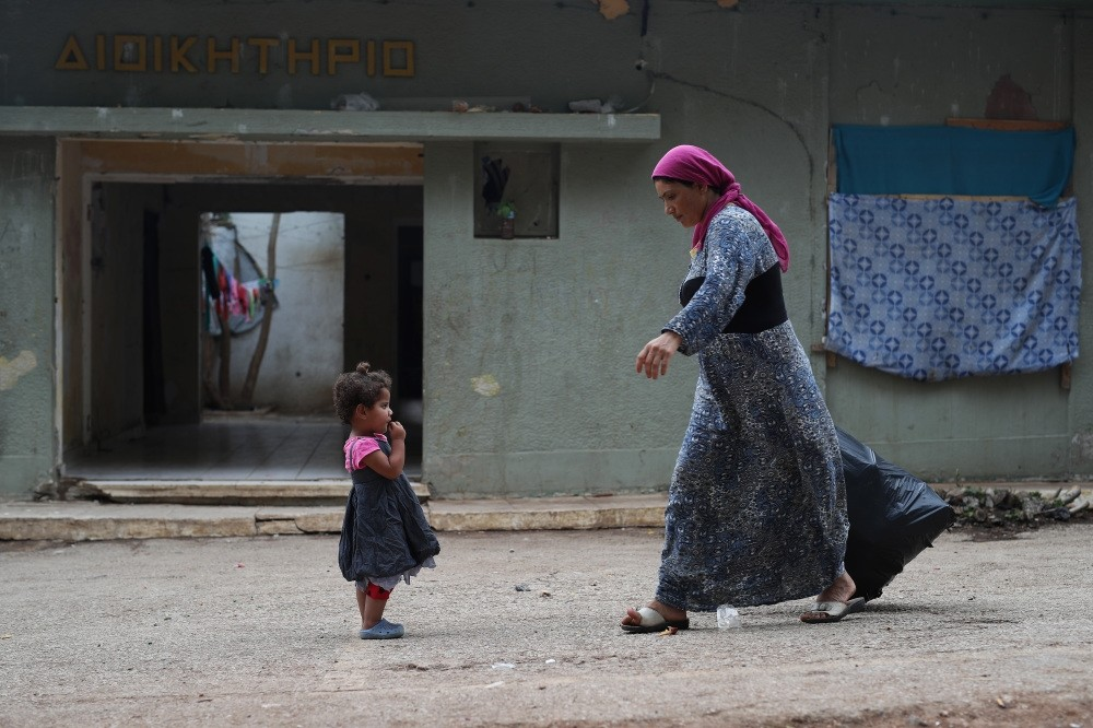 A Syrian woman carrying plastic bag with garbage at Ritsona refugee camp north of Athens, Sept. 8, 2016.