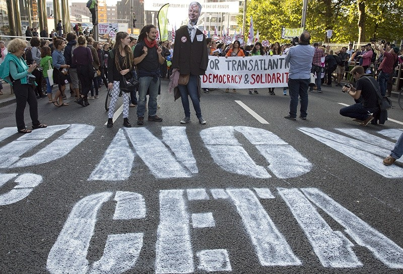 In this photo taken on Tuesday, Sept. 20, 2016, demonstrators walk over a spray painted sign on the street during a demonstration against international trade agreements in Brussels. (AP Photo)