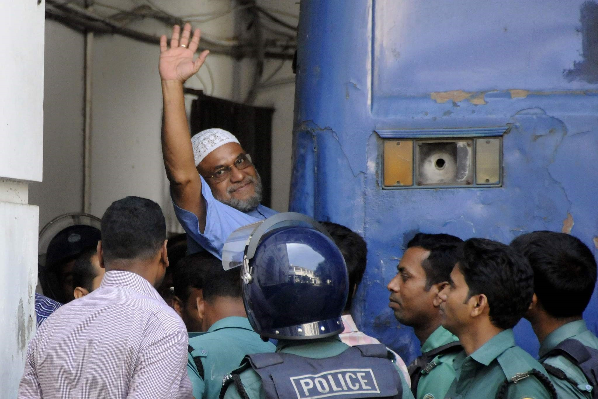 This file photograph taken on November 2, 2014, shows Bangladeshi Jamaat-e-Islami party leader, Mir Quasem Ali waving as he enters a van at the International Crimes Tribunal court in Dhaka. (AFP Photo)