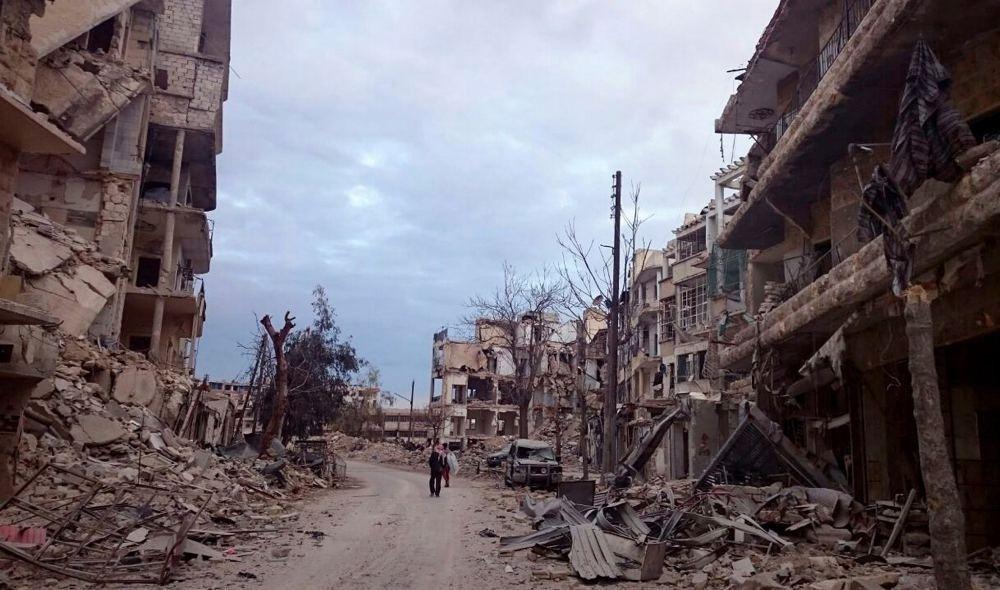 Men walk past damaged buildings and shops in the eastern Aleppo neighborhood of al-Mashhad, Syria, Dec. 8.