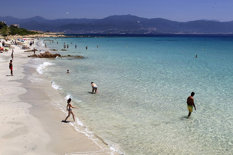People stand on the beach in Ajaccio on June 25, 2016 on the French island of Corsica. (AFP PHOTO)