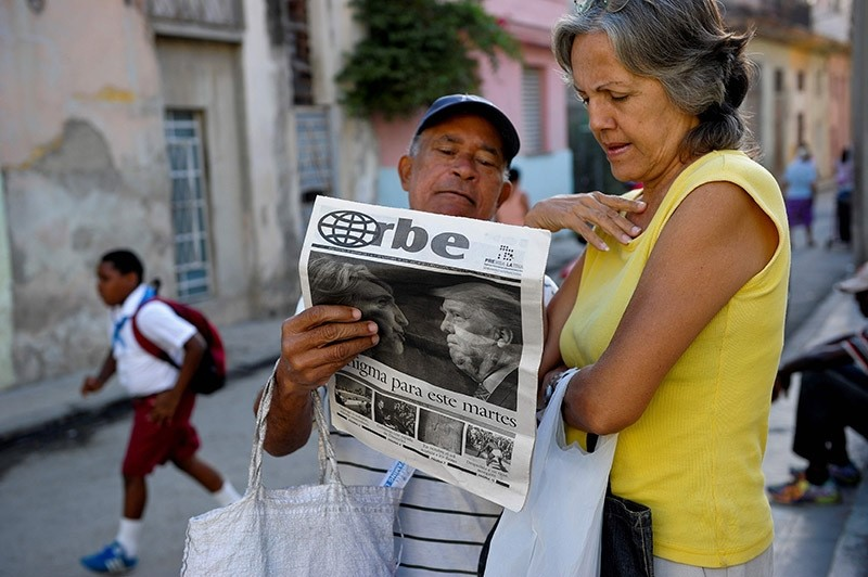 Cubans read a newspaper with its front page informing of the victory of US presidential candidate Donal Trump in a street of Havana, on November 9, 2016. (Photo AFP)