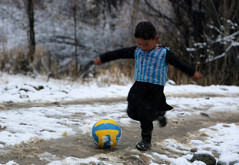 Afghan boy and Lionel Messi fan Murtaza Ahmadi, 5, wears a plastic bag jersey as he plays football in Jaghori district of Ghazni province. (AFP Photo)