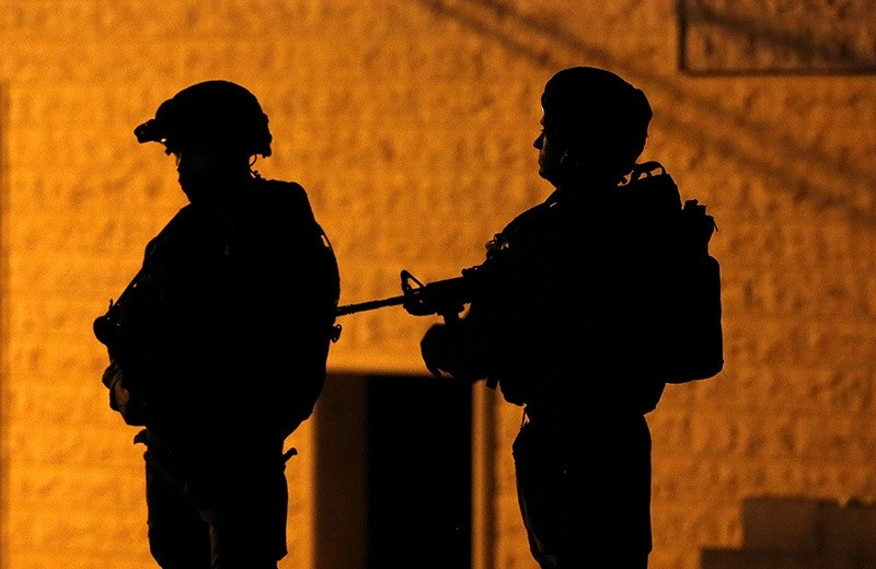 Israeli army soldiers are seen during a night raid as they purportedly arrested Palestinian Abed Abu Eram, in Yatta, south of the city of Hebron, The West Bank, 15 June 2016. (EPA)