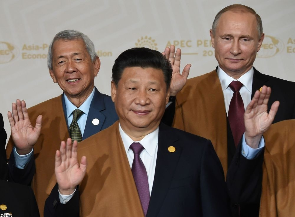 (L to R) Philippine Foreign Secretary Perfecto Yasay, Chinau2019s Xi Jinping and Russiau2019s Putin take part in the traditional u201cfamily photou201d on the final day of the Asia-Pacific Economic Cooperation Summit at the Lima Convention Centre in Lima.