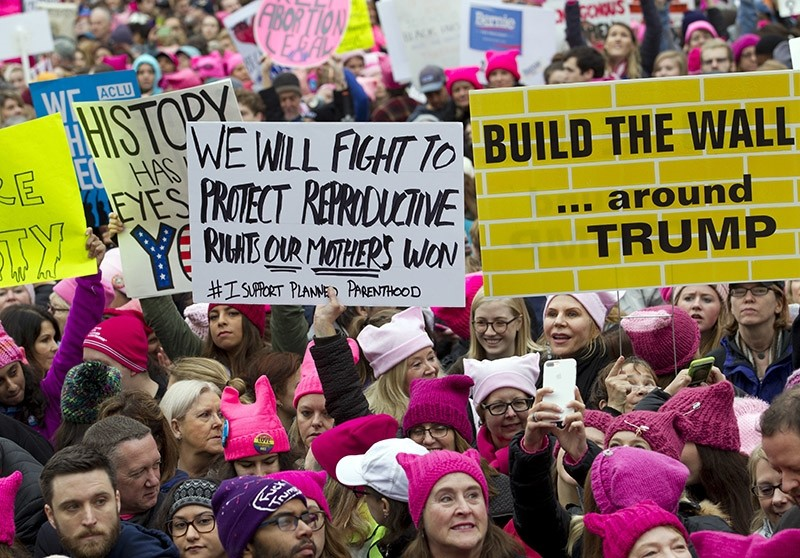 Women with bright pink hats and signs begin to gather early and are set to make their voices heard on the first full day of Donald Trump's presidency, Saturday, Jan. 21, 2017 in Washington. (AP Photo)