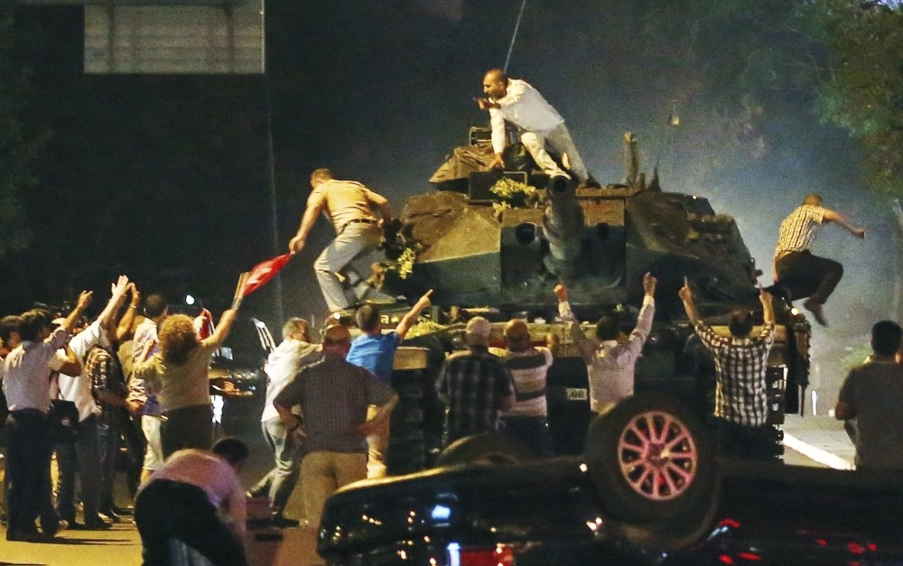 A tank moving into position as Turkish people clamber onto it, attempting to stop the Gu00fclenist military coup, in Ankara, July 16.