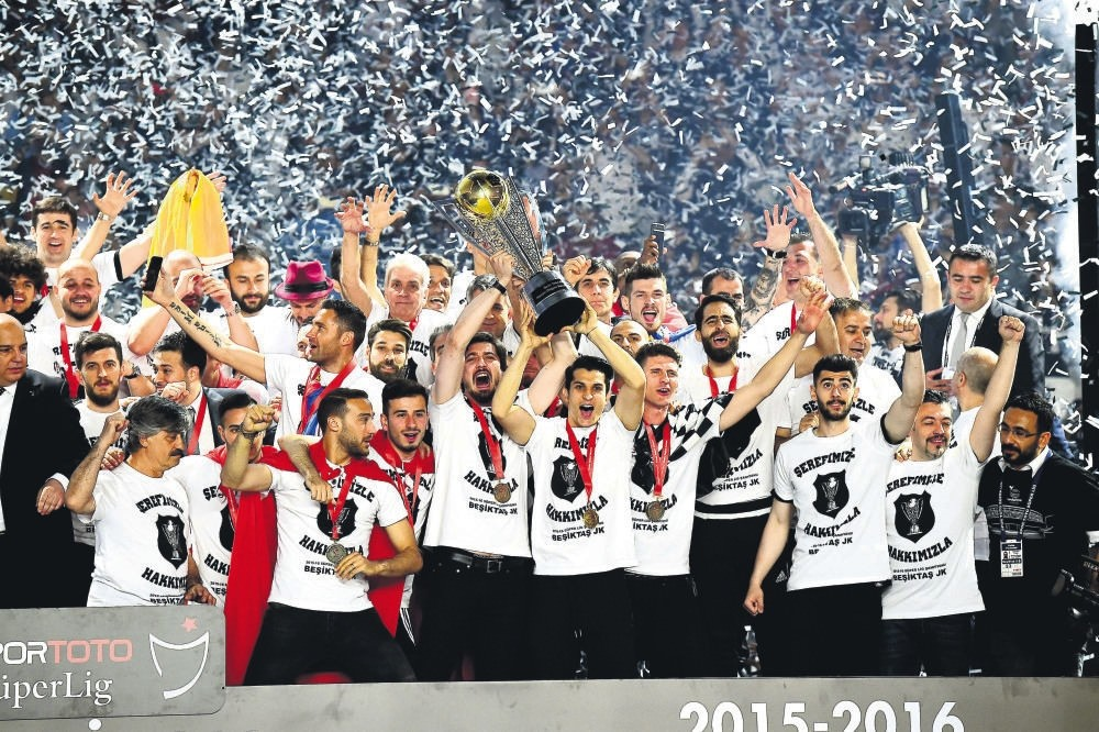 Beu015fiktau015f players hold the trophy during a victory ceremony at Vodafone Arena in Istanbul.