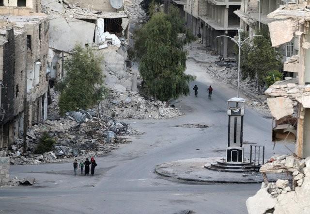 People walk past damaged buildings in the rebel-held Tariq al-Bab neighbourhood of Aleppo, Syria, October 5, 2016 (Reuters Photo)